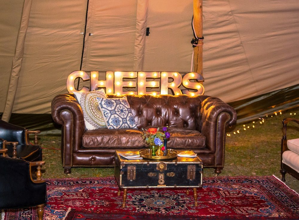 Featured Frenchie Rentals: Sebastien Leather Sofa, Christophe Club Chairs, Vintage Trunk Table, Cheers Marquee Sign, Basile Perisan Rug, Assorted Pillows + Decor