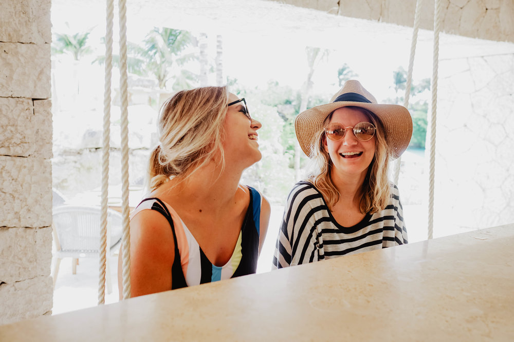 Two women laughing at the bar at Hotel Xcaret Mexico