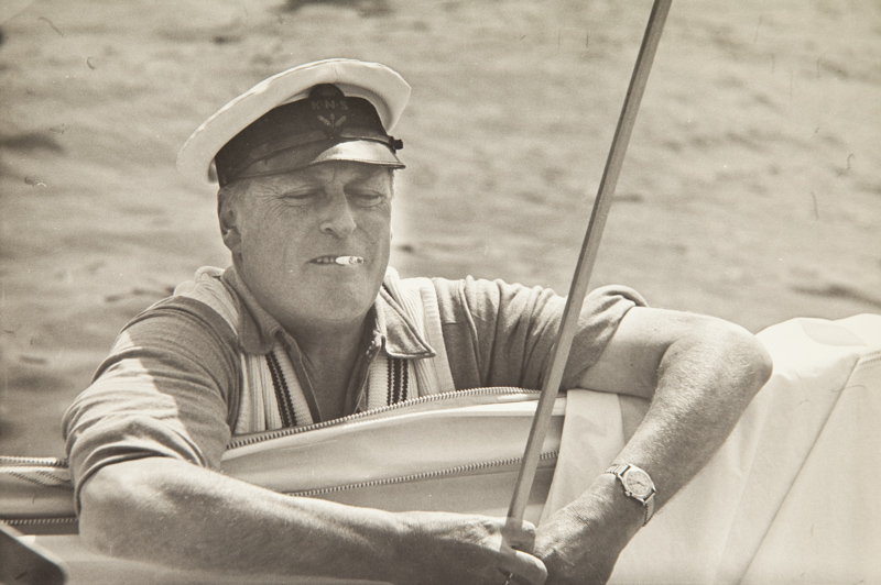 ....H.M. Olav, the king of Norway, was one of the skippers competing for the word championship of 5.5 m class in 1960. He did surprisingly well with his NORNA IX finishing usually as tenth in a fleet of nearly 50 best ones in the world. In his friendly, non-etiquette ways the king achhieved immense popularity. He always had a cigarette burning when setting sails. Photo: Martti Vuorenjuuri.. Norjan kuningas Olav osallistui vuonna 1960 maailmanmestaruuskisoihin 5.5 m -luokassa. Hänen NORNA IX -veneensä miehistöineen purjehti hyvin ollen yleensä parhaan kymmenen veneen joukossa 50 veneen laivueessa. Olavin ystävällinen, mutkaton olemus valloitti muut purjehtijat ja tupakka paloi aina huulessa hänen viikatessa purjeitaan. Kuva: Martti Vuorenjuuri....