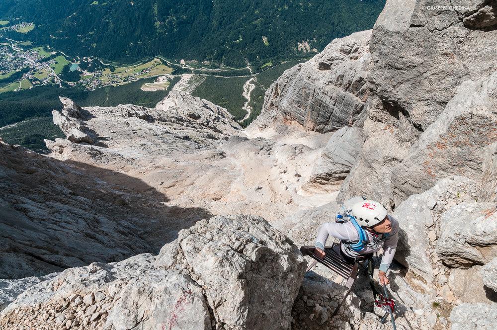 Le scalette accompagnano spesso i dislivelli lungo la Cengia del Banco _ Sorapiss Dolomiti - in basso l'abitato di San Vito di Cadore_ Foto @giuseppeghedina.com