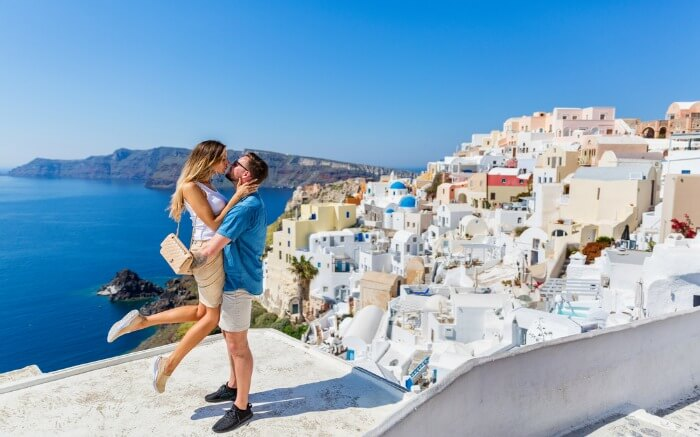Young-couple-looks-down-on-the-landscape-of-the-island-of-Santorini-ss08082017.jpg