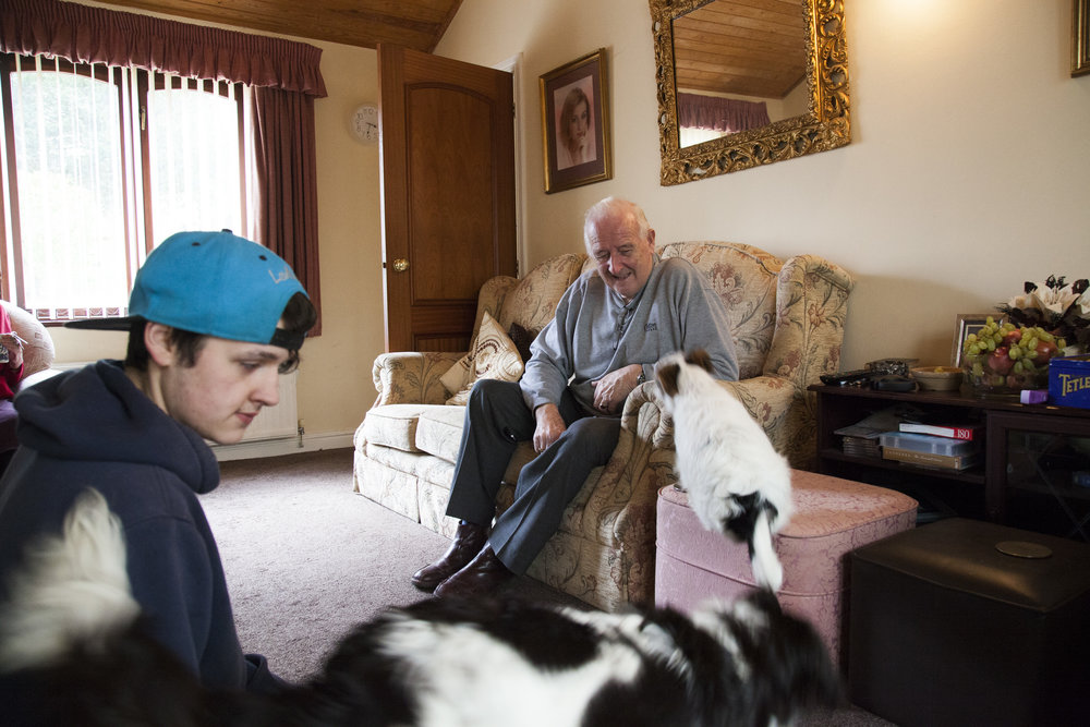 Graham and his grandson Luke playing with dogs in his living room.
