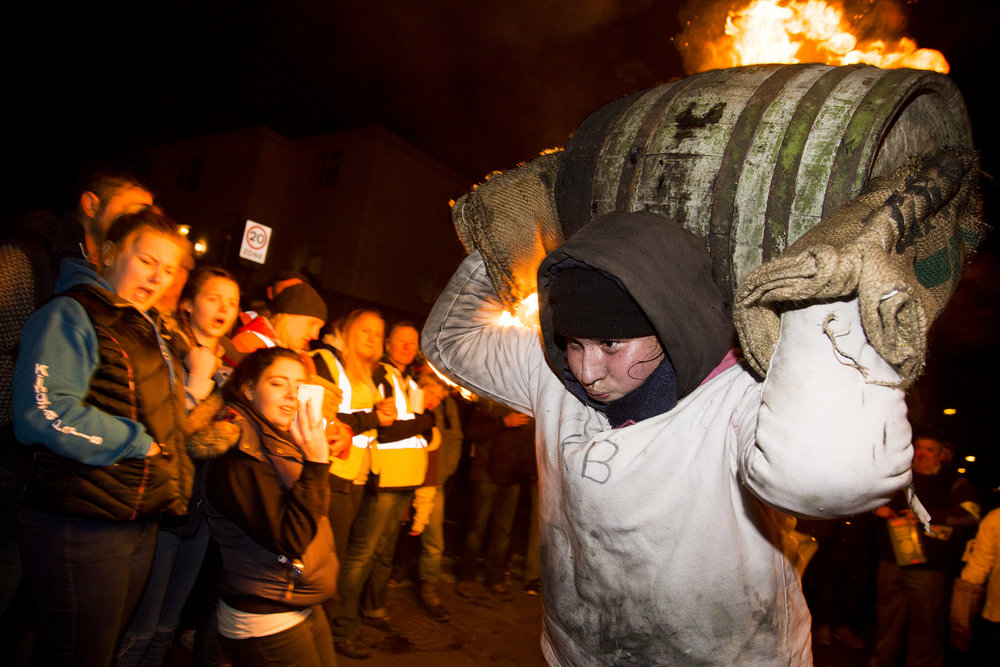A teenage girl carries a flaming tar barrel through Mary's St.Ottery on Guy Forks night 2016. Ottery St. Mary is internationally renowned for its Tar Barrels, an old custom said to have originated in the 17th century, and which is held on November 5th each year. Each of Ottery's central public houses sponsors a single barrel. In the weeks prior to the day of the event, November 5th, the barrels are soaked with tar. The barrels are lit outside each of the pubs in turn and once the flames begin to pour out, they are hoisted up onto local people's backs and shoulders.