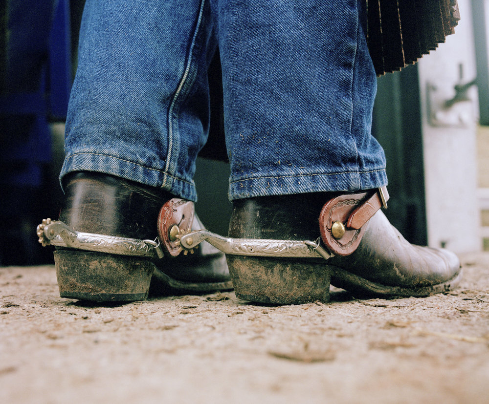 Nick Michelle's riding boots, standing on the ground of Hemborough farm. The rodeo riders wear original gear to compete and ride in.