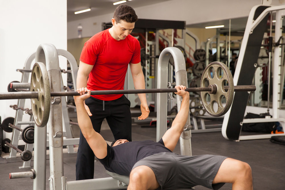 Man Spotting His Friend On A Bench Press