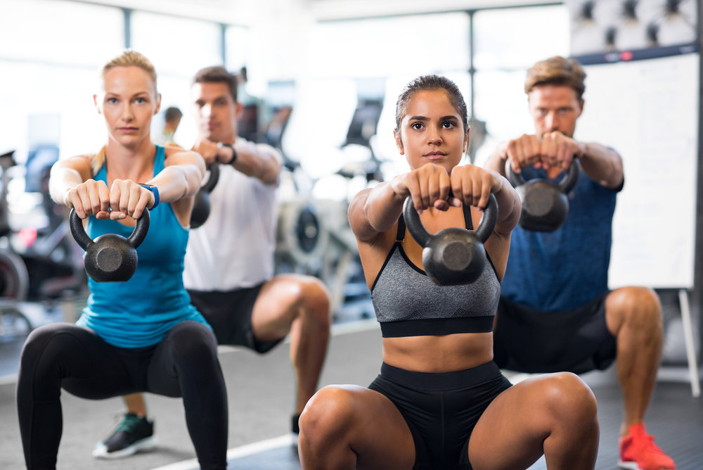 Women and men exercising with kettlebells in gym. Group of young