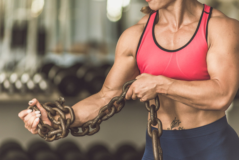 The Bodybuilding Girl Is In The Gym With A Chain In Her Hands.