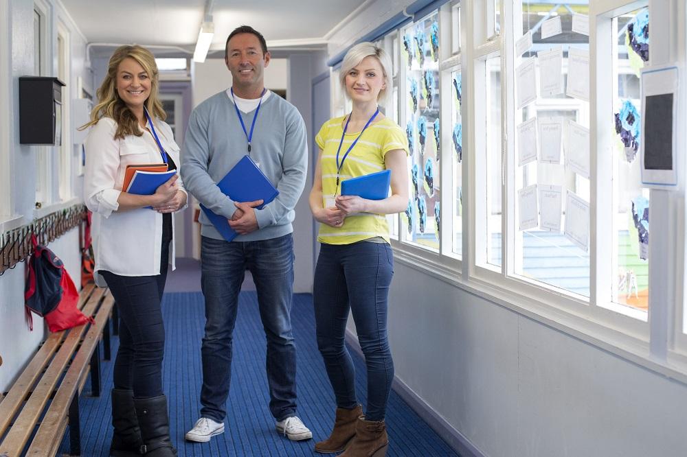 Three Teachers in School Corridor