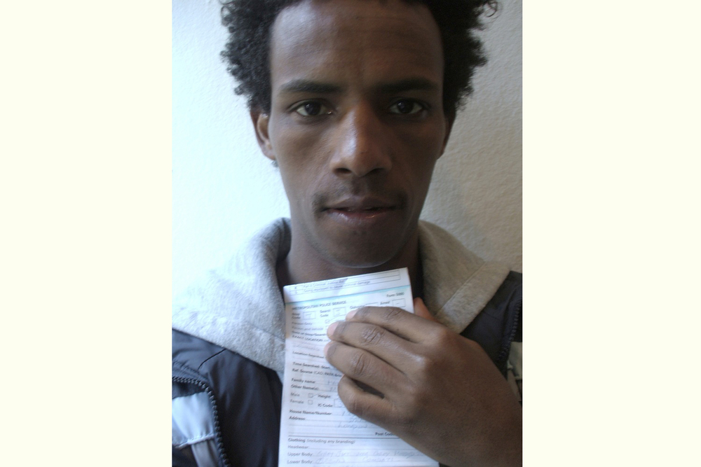This picture is interesting and makes me wonder.  It was the first time I came into contact with the police in England.  I was stopped and searched when I was waiting for Crispin outside Downing Street.  Afterwards I took this self-portrait holding the piece of paper they gave me.     Mussie Haile, excerpt from They Seem To Be Ours But They Are Not … , New Londoners (PhotoVoice / Trolley 2008)