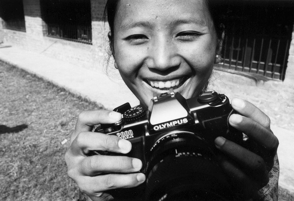 Playing with camera outside the exhibition, PhotoVoice participant, Kathmandu, Nepal 2003  (c) Tiffany Fairey