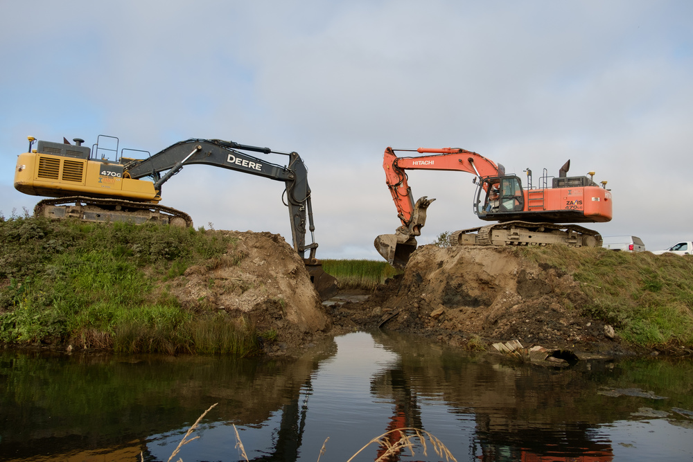 Excavators began work early in the morning on an outgoing tide breaching the old dike.