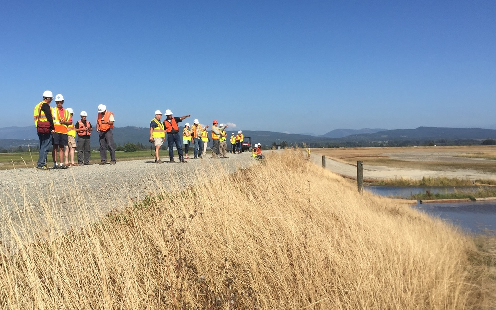 Project partners gather on the new dike to watch the incoming tide.