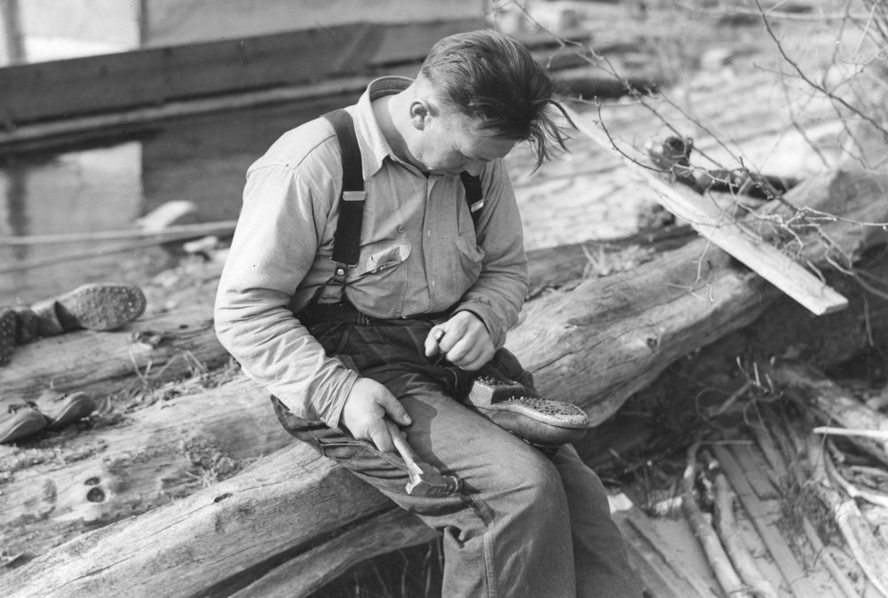 Bill Engstrom caulking his boots. It was necessary to re-caulk as often as once a week to avoid becoming slick shod. Each man did the job himself. Holes in the outer sole of the boot, left by prying out the dulled caulk, were pegged full of wood. Then the new caulk was driven into the wood. When the wood swelled because of moisture, the caulk became an inseparable part of the boot. (Photo © Forest History Society)