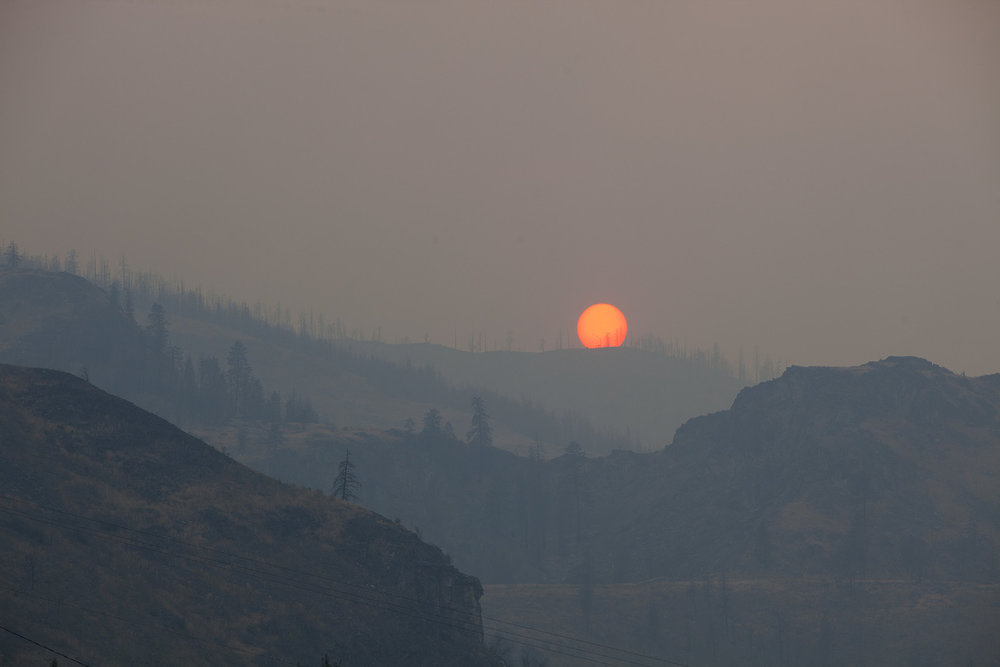 Red sun and smoke as seen from lower Methow River area between Pateros and Methow.  Photo by John Marshall.