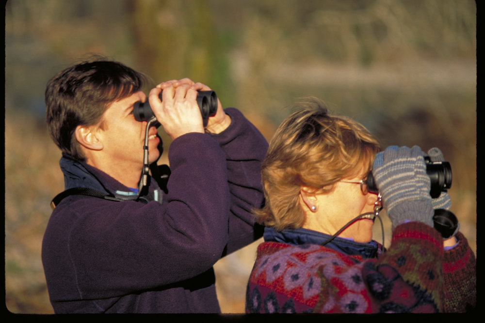Bob Carey and Libby Mills with binoculars along the Skagit River in 2007.  Photo by Peter Dunwiddie/TNC.