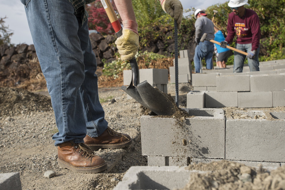 Depaving project - Volunteers work to build a community garden in Kent, Washington. Volunteers and staff continue to build garden plots with cinderblock and fill soil. Photo © Hannah Letinich.