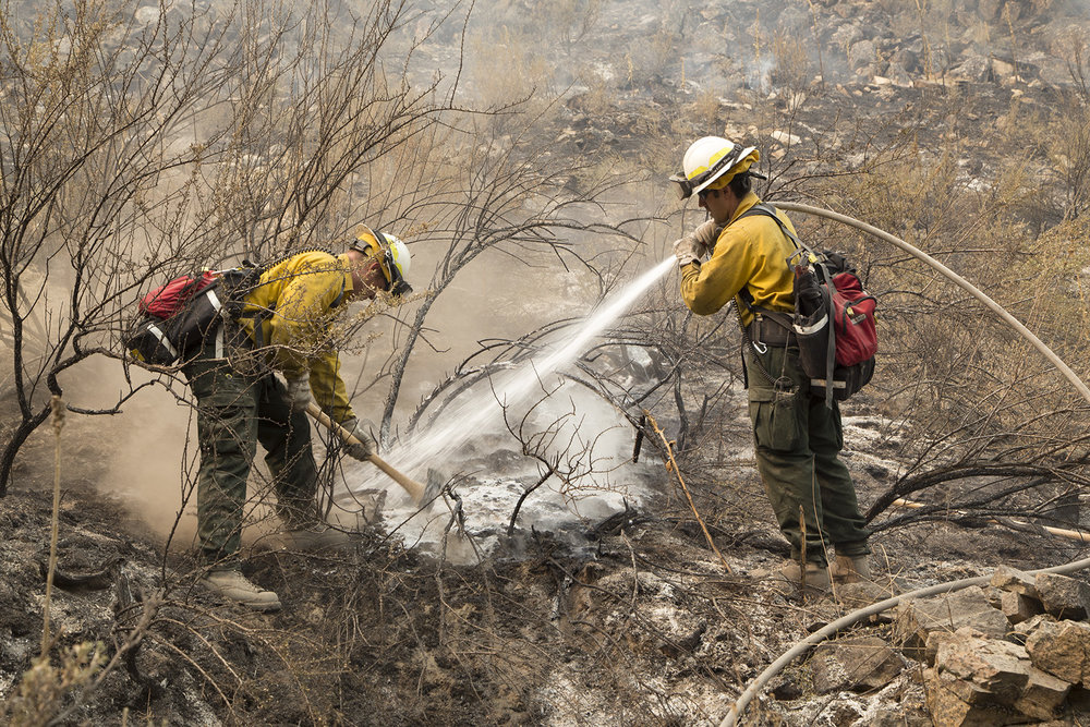 Members of Seattle City Fire Department, hose down hot-spots with foam at First Creek Fire along Lake Chelan.  A mobile home just out of picture was being protected.  Photo by John Marshall.