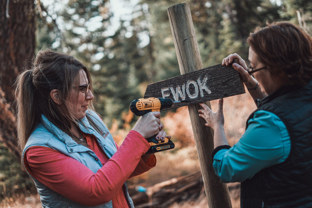 "County Commissioner Laura Osiadacz and The Nature Conservancy's Darcy Batura drill in the first sign of the new ""Ewok"" trail that REI volunteers built. Phot © Courtney Baxter"