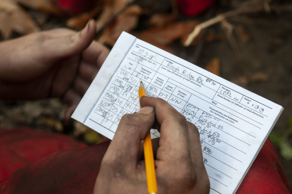 A TREX participant records weather measurements during the Oct. 4 burn. Dry forest prescribed fires are conducted in the fall and spring when conditions, like soil moisture, are right to ensure the fire stays under control. © Nikolaj Lasbo / TNC