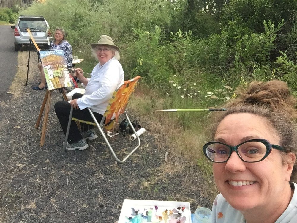 Artist Jack Cook Mack paints in Moses Coulee as part of a workshop organized by Americorps Volunteer Coordinator Kmbris Bond, right