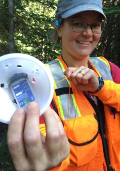 Hydrologist Susan Dickerson-Lange shows off a temperature sensor that will track snow melt at a research site. Photo by The Nature Conservancy.