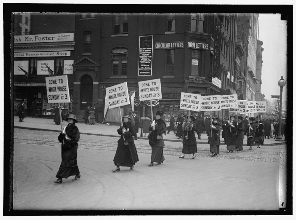 WOMAN SUFFRAGE. MARCHING WITH INV. SIGNS
