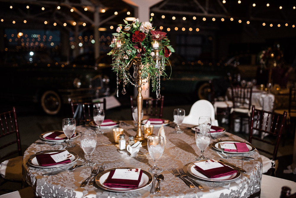 tall Burgundy and greenery centerpiec at Americas Packard Museum wedding