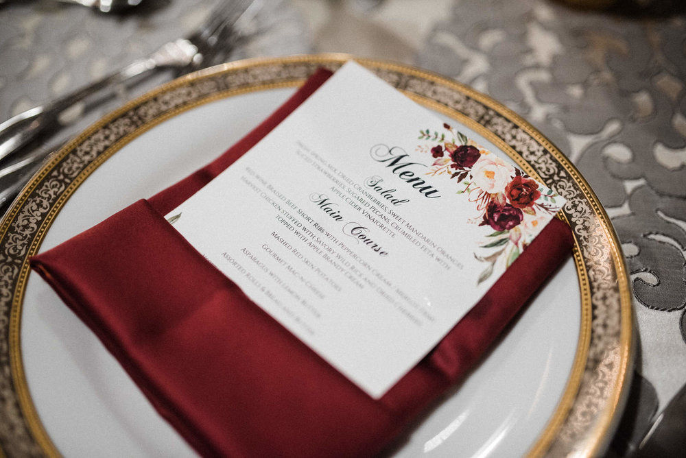Place setting with burgundy napkin and floral theme menu card at Americas Packard Museum wedding