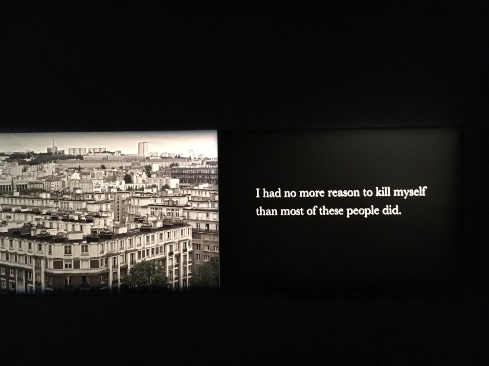 "A phrase from Houellebecq's 2015 novel, Submission: ""I had no more reason to kill myself than most of these people did,"" on the right panel of a large triptych at ""Michel Houellebecq: French Bashing"" art exhibit in New York. Photo Credit: Joel Whitney"
