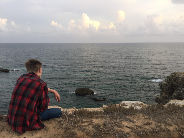 teenage boy in a red flannel shirt sitting on a rock overlooking the ocean