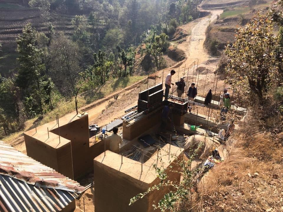 A building nearby being constructed with rammed earth