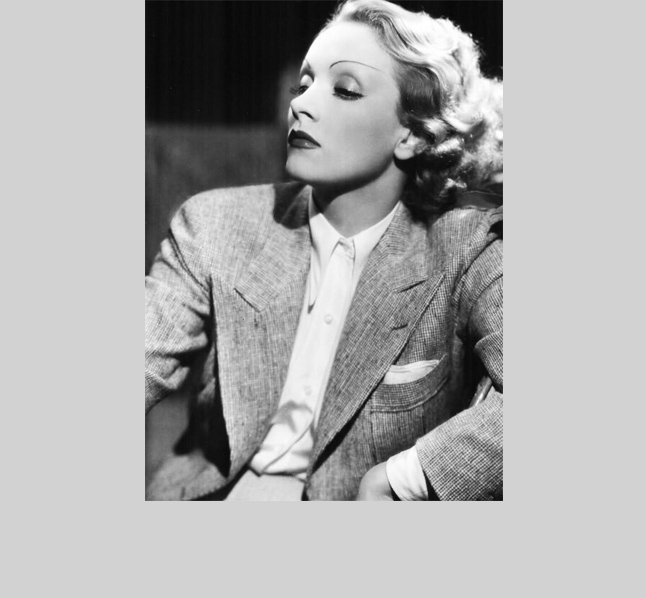Marlene Dietrich    gives gorgeous tomboy nonchalance in a double-breasted peaked-lapel dream. The German actress and singer shattered the feminine ideal as early as the 1920's--eschewing gowns and dresses in favor of suiting. Dietrich are her suits, left behind her, a trail of intrigue and broken hearts.