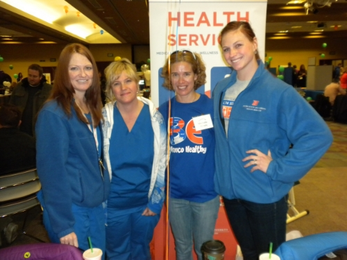 Holly (far right) at a health fair with members of University Health Services.