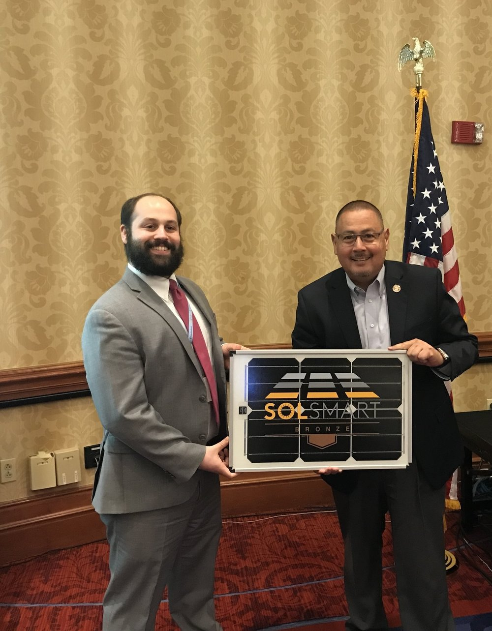 SolSmart staff (left) presents Maricopa County, AZ Supervisor Steve Gallardo (right) with a Bronze SolSmart panel to commemorate the county's designation.