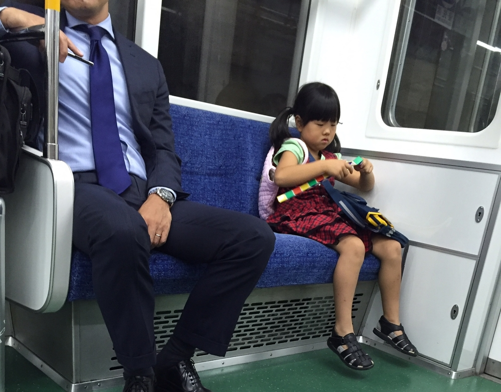 small child on subway plays with complicated toy
