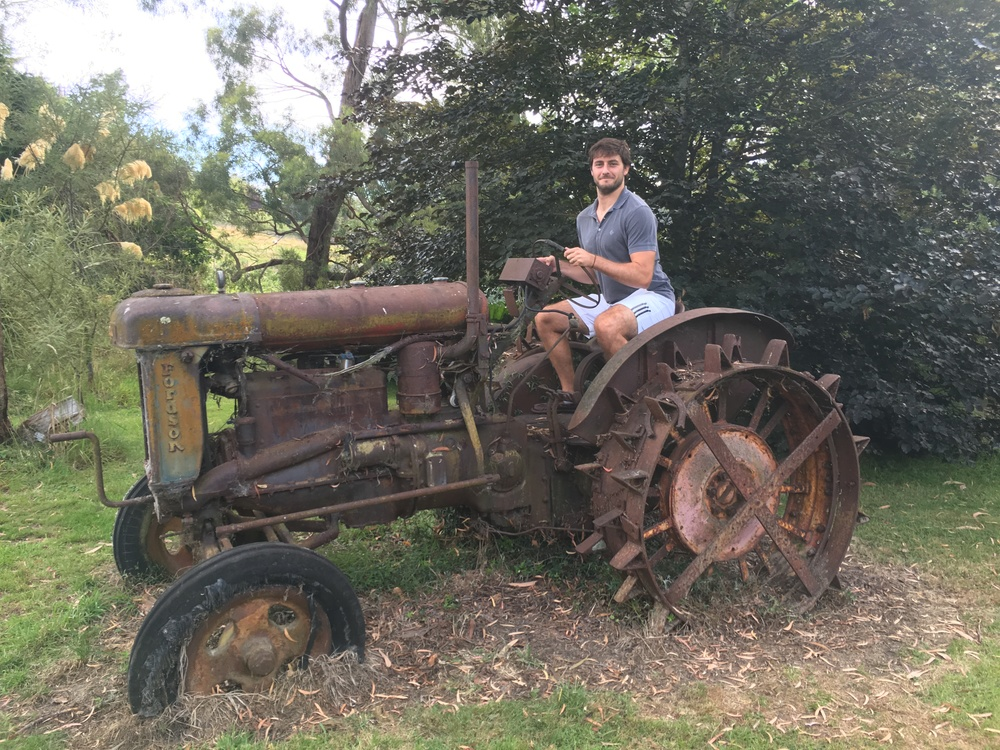 Cole awkwardly squats on a tractor