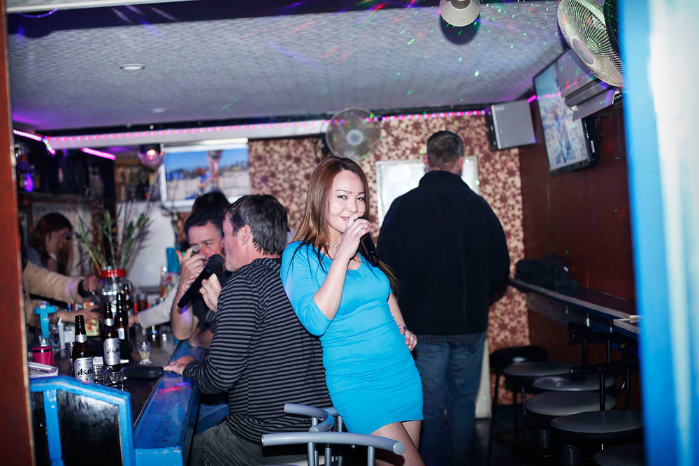 A woman singing karaoke in sailor town's bar Sasebo, Japan 2015