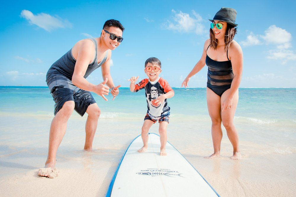 kid on surfboard mom dad ocean hawaii beach