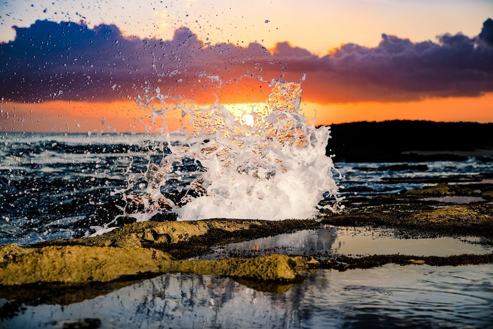 wave splashing on hawaii rocky shore at sunset
