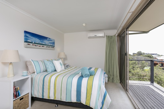 Main queen bedroom (upstairs) with bay views and door to balcony