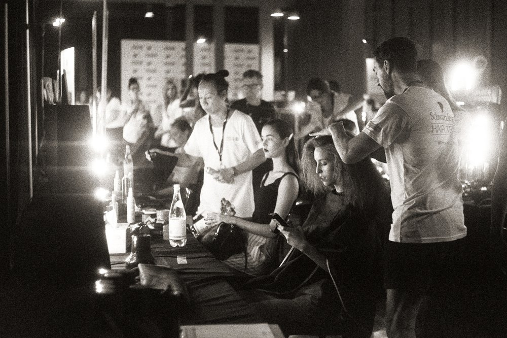 Models are prepped by a zoo of hair and makeup artists backstage.