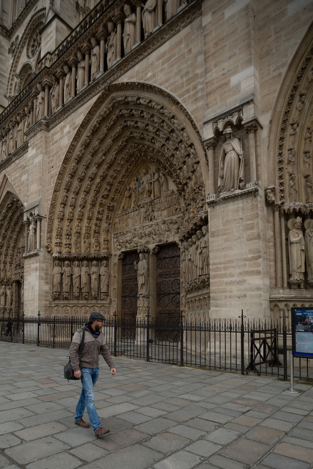 A man admires the cathedral's famed carvings that tower over the doorways of Notre Dame.