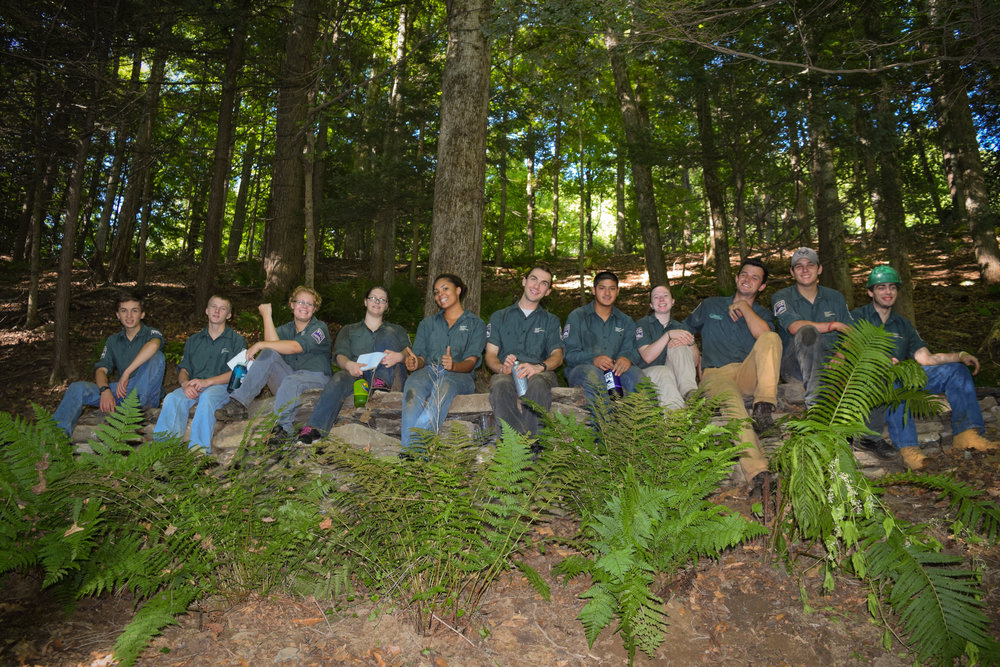 The crew atop the 48-square-foot stone retaining wall they built