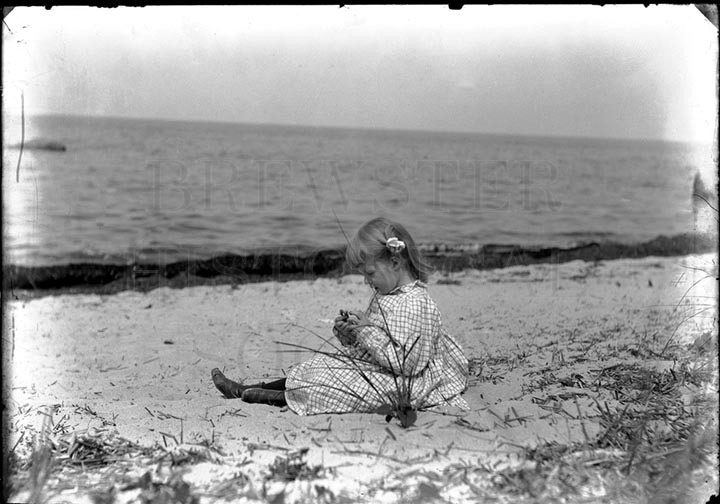 58. 1970.10.T131 Child Sitting on Beach c.1900 – photographer unknown