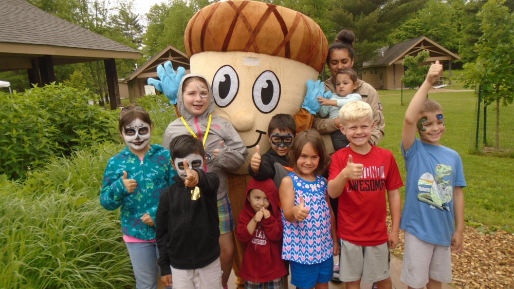 Nate the Nature Nut mascot (center) is surrounded by new friends during the recent Dunes Learning Center Open House. (Sue Ellen Ross/Post-Tribune)  Sue Ellen RossPost-Tribune
