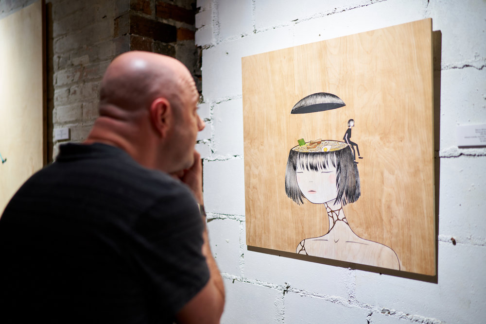 Local Artist Wyatt Eddy exploring a Kintsugi Ramen Girl up close. Photo: Jeffrey Enriquez