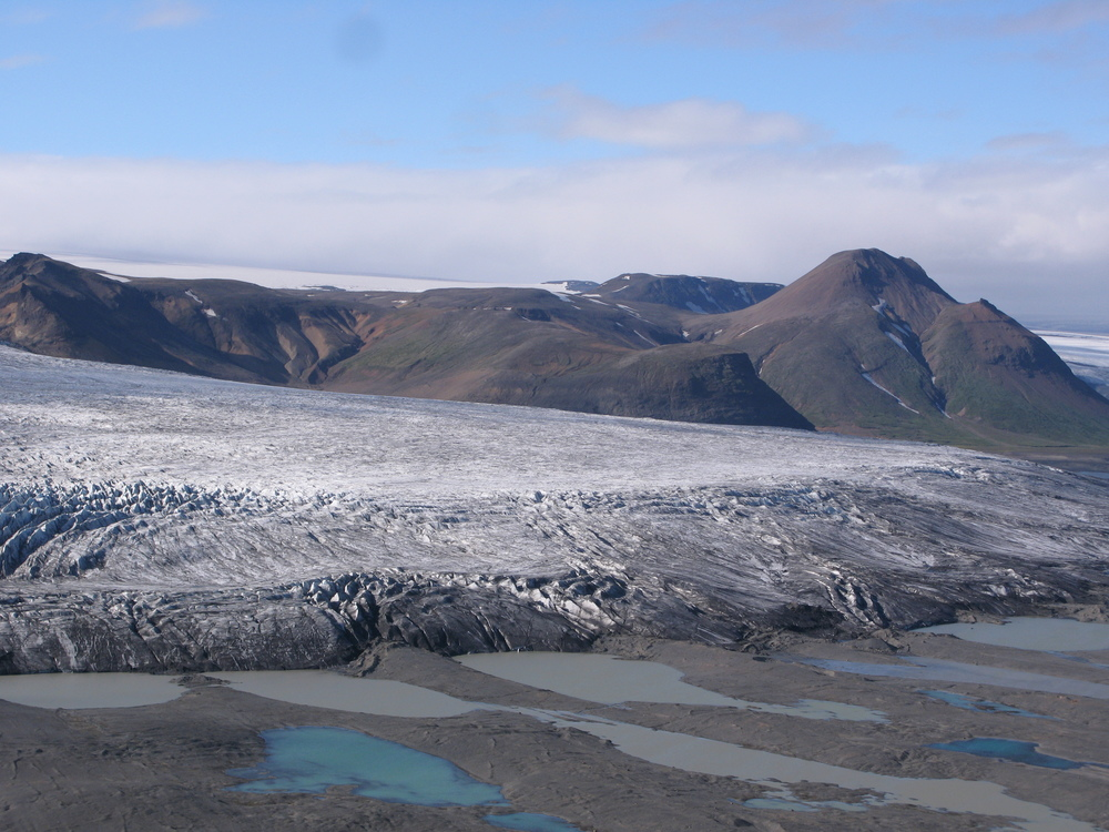 "[Fig 1] A photo of Mulajökull glacier in Iceland.  The drumlins are the oblong hills emerging from the edge of the ice as it melts. Our knowledge of drumlin formation is very limited because these are the only ones known to be actively forming under an ice sheet. (Thanks to Mark Johnson for the photo)     Normal   0           false   false   false     EN-US   JA   X-NONE                                                                                                                                                                                                                                                                                                                                                                                                                                                                                                                                                                                                                                                                                                                                                                                                                                                             /* Style Definitions */  table.MsoNormalTable 	{mso-style-name:""Table Normal""; 	mso-tstyle-rowband-size:0; 	mso-tstyle-colband-size:0; 	mso-style-noshow:yes; 	mso-style-priority:99; 	mso-style-parent:""""; 	mso-padding-alt:0cm 5.4pt 0cm 5.4pt; 	mso-para-margin-top:0cm; 	mso-para-margin-right:0cm; 	mso-para-margin-bottom:10.0pt; 	mso-para-margin-left:0cm; 	mso-pagination:widow-orphan; 	font-size:10.0pt; 	font-family:""Cambria"",serif; 	mso-ascii-font-family:Cambria; 	mso-ascii-theme-font:minor-latin; 	mso-hansi-font-family:Cambria; 	mso-hansi-theme-font:minor-latin; 	mso-ansi-language:EN-US; 	mso-fareast-language:JA;}"