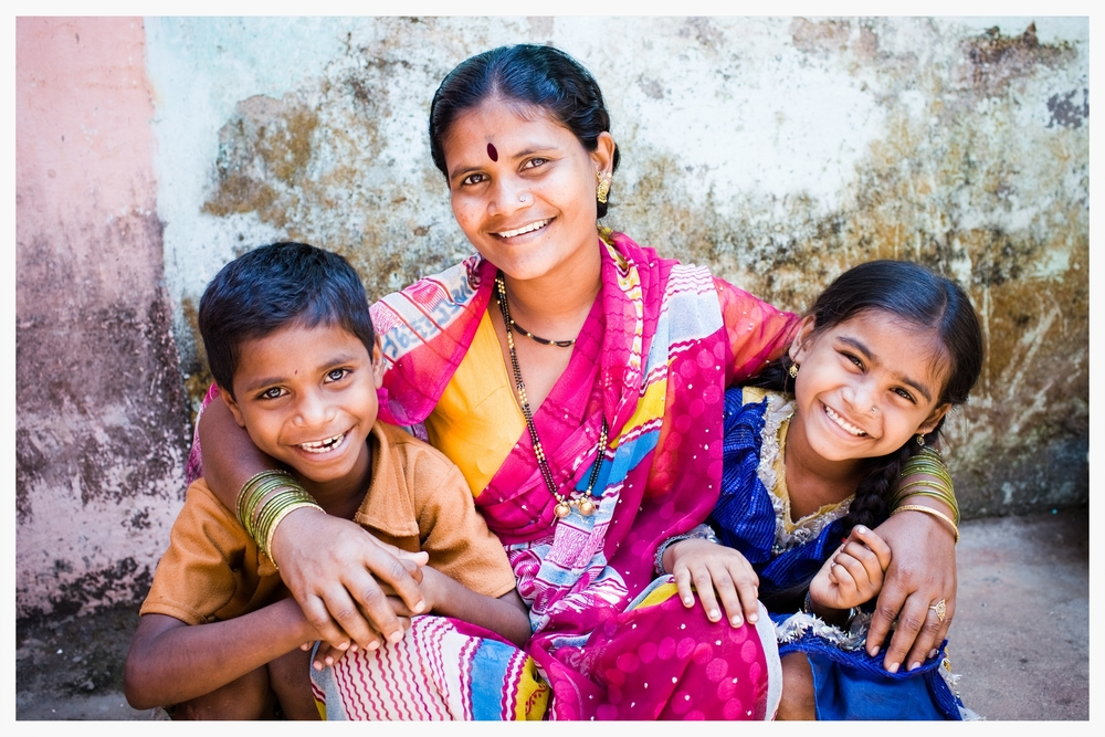 Chaya sits with her two youngest children, Vishal and Nisha.