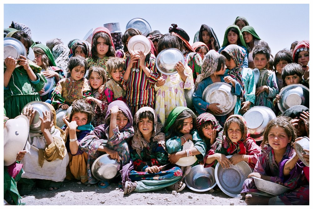 Afghan girls wait patiently in the mid-day heat to collect their ration of soup and bread. Western desert near Herat, Afghanistan. Photo © Marcus Perkins