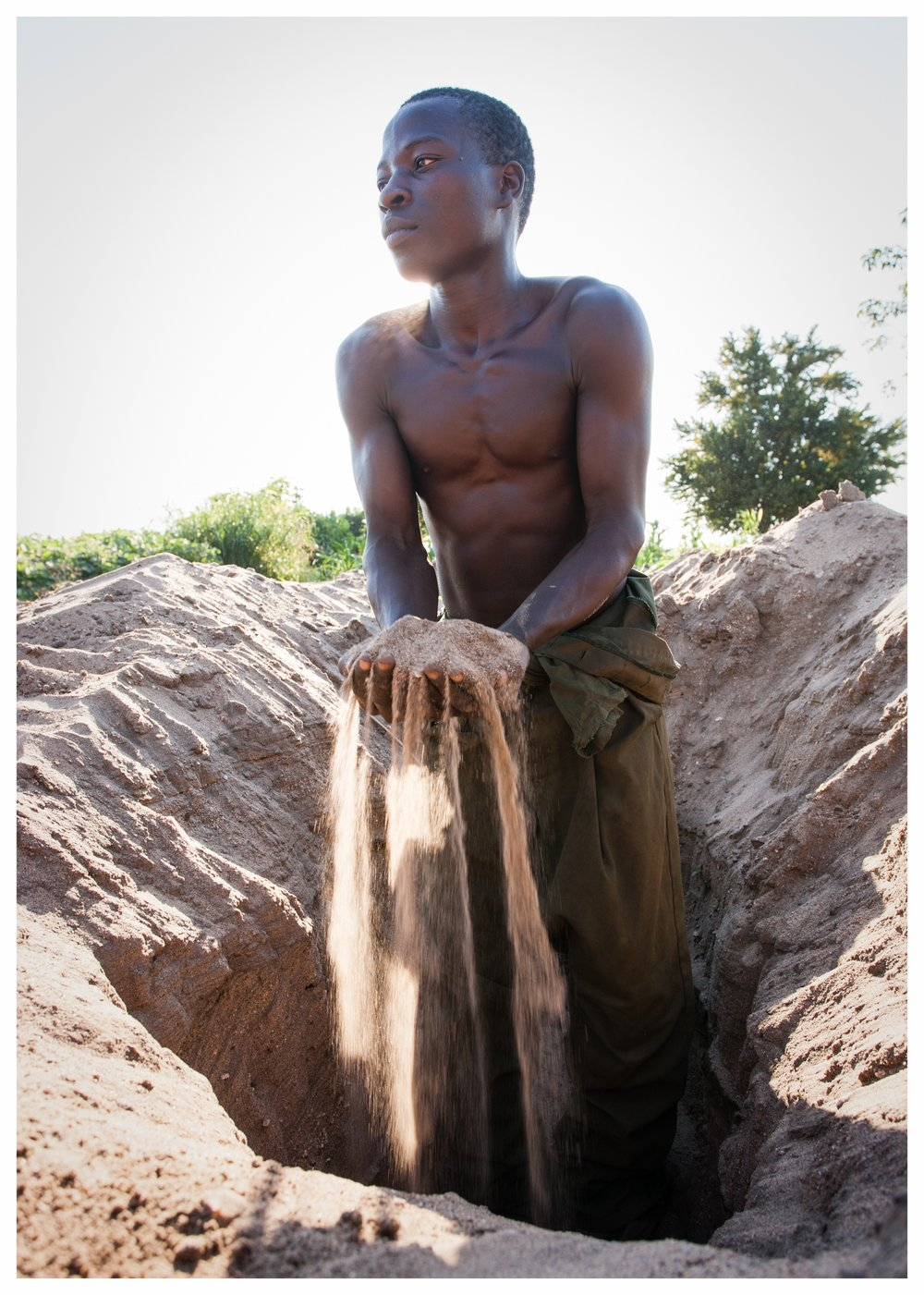 Andrew digs through sand to find fertile soil for his crop. Fombe, Chikwawa, Malawi. Photo © Marcus Perkins